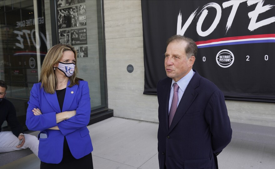 Michigan Secretary of State Jocelyn Benson (left) and Detroit Pistons Vice Chairman Arn Tellem talk about voting last Thursday, when balloting began in the state. The Pistons are allowing their arena to be used as a polling station.