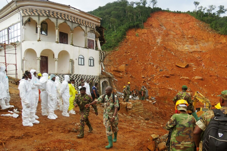 Search and rescue team members and soldiers work near a mudslide site and a damaged building near Freetown, Sierra Leone, on Tuesday.