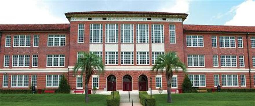 Leon High School, a classic, red-brick facade, lined with palm trees and green grass