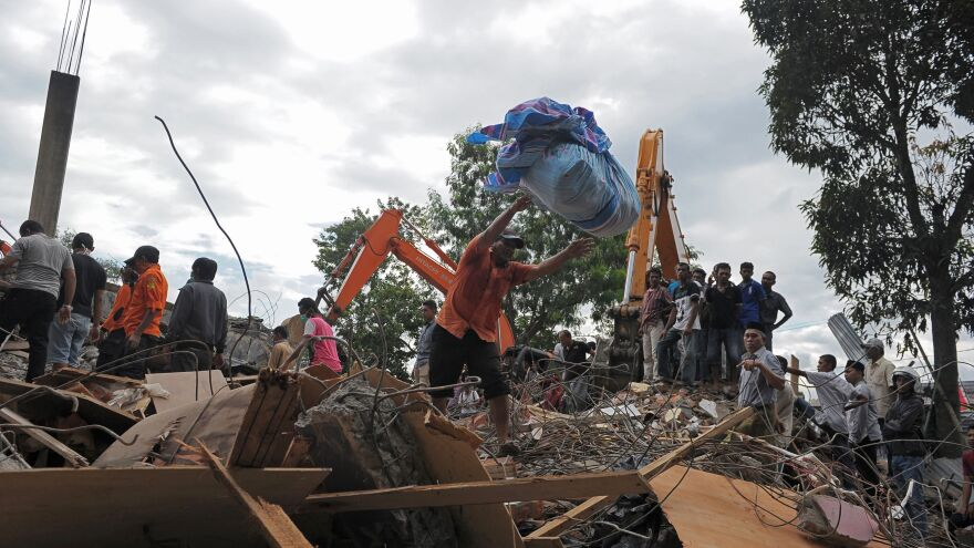 Members of a search and rescue team look for earthquake survivors trapped in rubble in Pidie Jaya, in Indonesia's Aceh province, on Wednesday. A magnitude 6.5 earthquake in the region has killed scores of people.