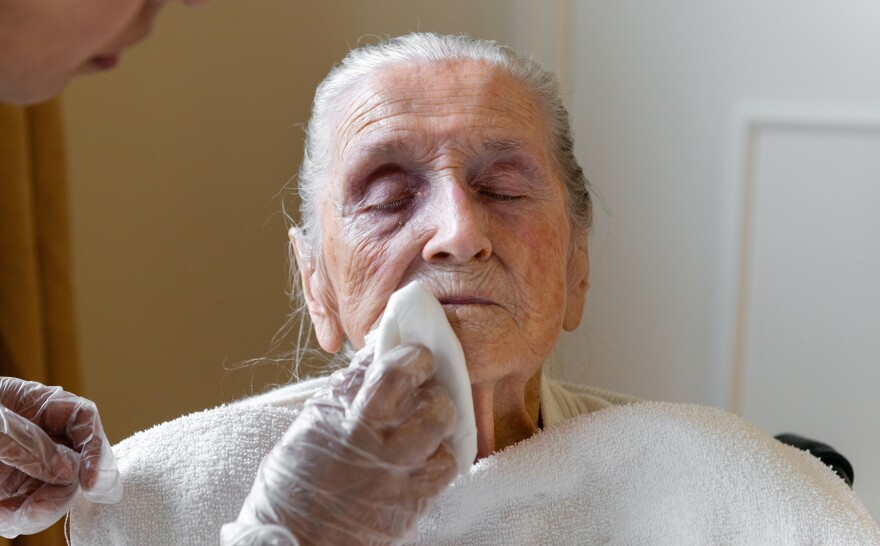 A certified nursing assistant wipes Neva Shinkle's face with chlorhexidine, an antimicrobial wash. Shinkle is a patient at Coventry Court Health Center, a nursing home in Anaheim, Calif., that is part of a multicenter research project aimed at stopping the spread of MRSA and CRE — two types of bacteria resistant to most antibiotics.