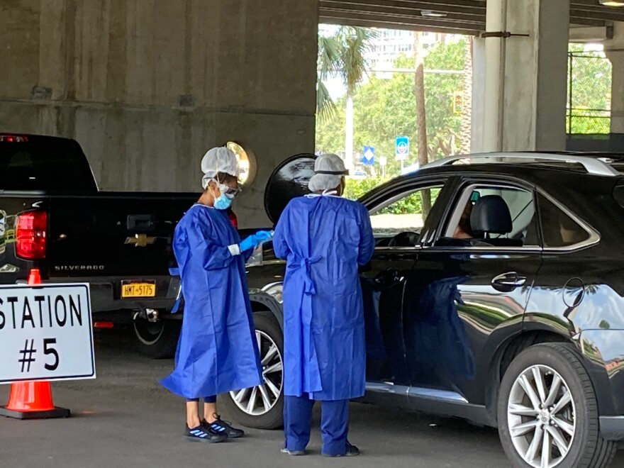 medical professionals conduct drive-through testing outside a vehicle in a parking garage