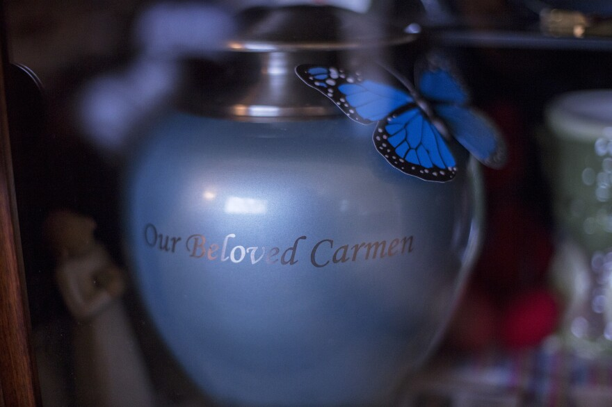 The blue urn holding Carmen's ashes rests with photos and drawings in a glass cabinet in the family's living room.