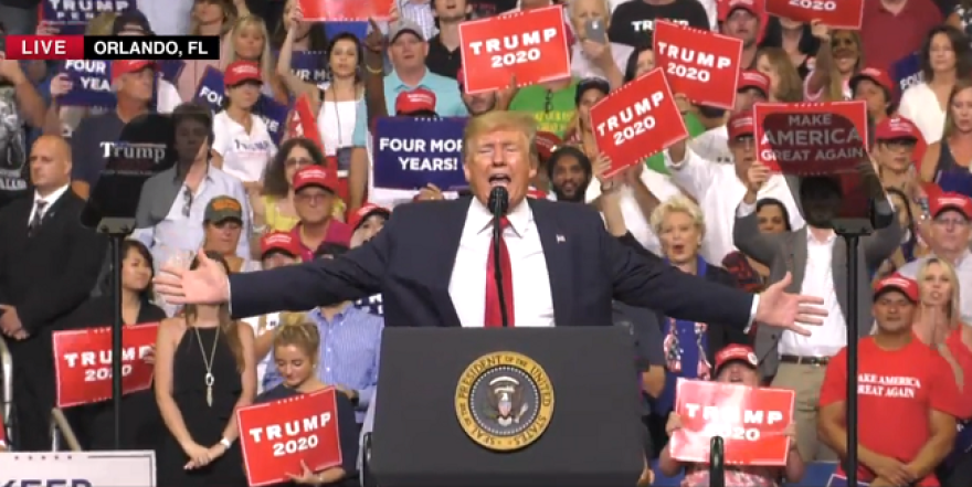 Crowd holding re-election signs behind President Trump at podium.