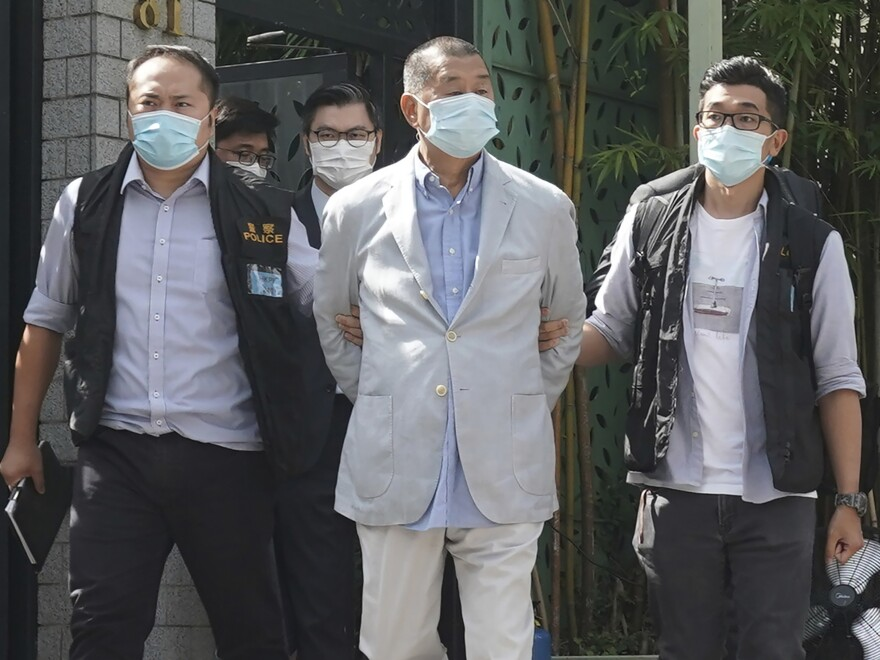 Hong Kong media tycoon Jimmy Lai, center, is arrested by police officers at his home in Hong Kong on Monday. Hong Kong police arrested Lai and raided the publisher's headquarters in the highest-profile use yet of the new national security law Beijing imposed on the city after protests last year.