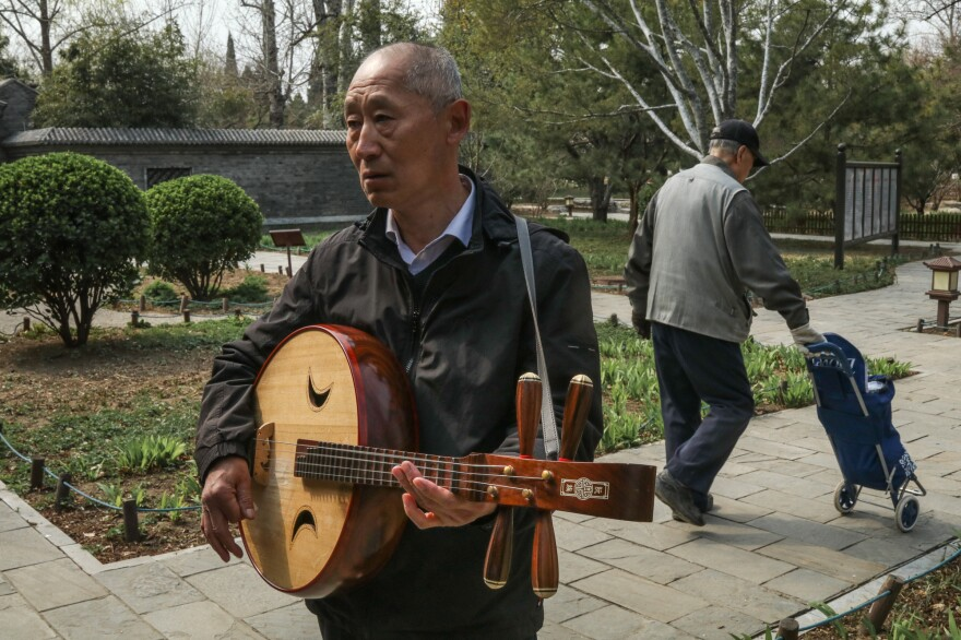 Yang Jiancheng, 63, taught himself to play the <em>ruan</em>, a four-stringed, mandolin-like instrument.