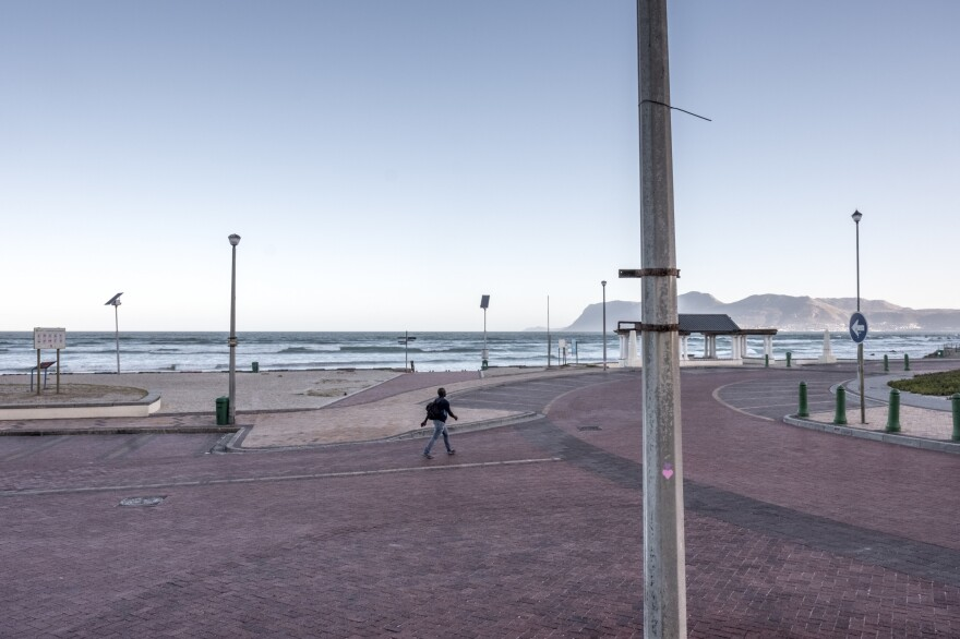 A man walks along the empty seafront at Muizenberg, Cape Town, South Africa, on day three of the country's coronavirus lockdown.