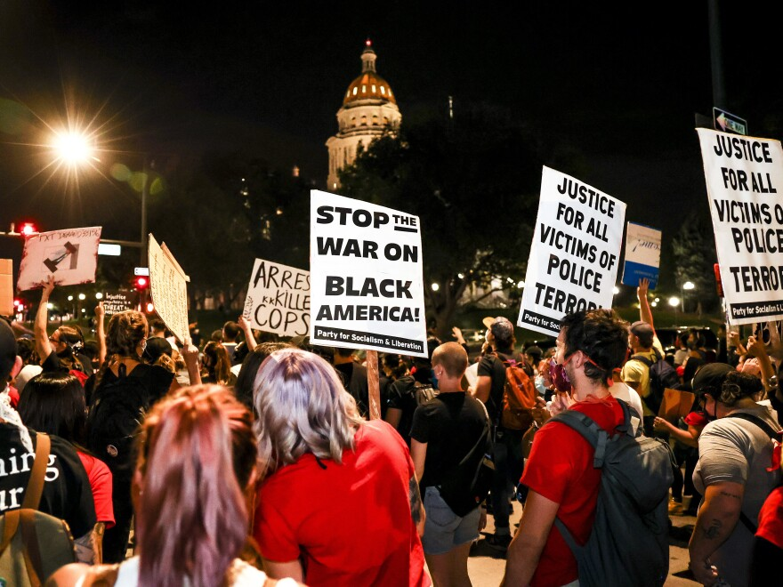 People protest the grand jury decision in the Breonna Taylor case in front of the Colorado State Capitol in Denver Wednesday. As the protest was breaking up, a motorist drove through a small crowd of protesters — who had yelled at him to turn around.