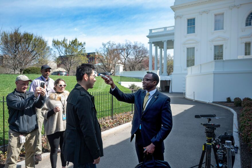 A doctor from the White House physician's office checks temperatures on a journalist outside the press briefing room in March.