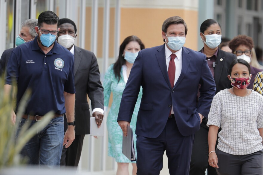 Florida Gov. Ron DeSantis, center, arrives for a news conference during the new coronavirus pandemic, Thursday, May 14, 2020, in Doral, Fla. DeSantis has signed an executive order for the reopening of Miami-Dade and Broward counties on May 18. (AP Photo/Lynne Sladky)