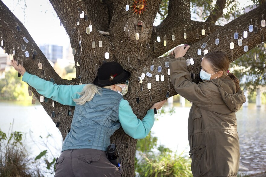 Valerie Romness  and Emmy Sawvel hug a tree with tags on it symbolizing homeless people who died in Austin this year.