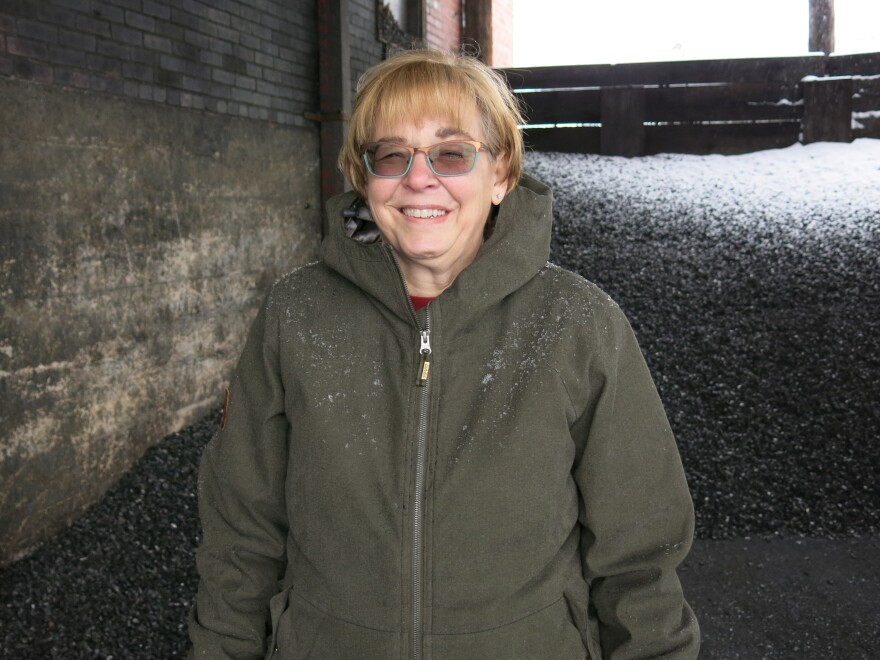 Kelly Brown stands in front of a pile of coal. Her family's business, F.M. Brown's Sons, has sold coal for nearly a century.