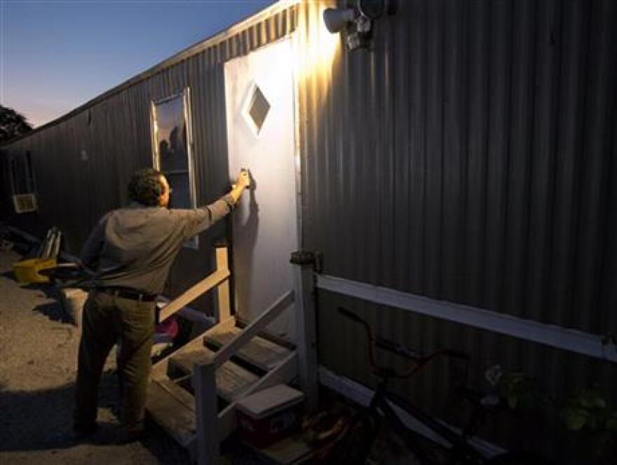 In this Thursday, Nov. 12, 2015 file photo, Antonio Tovar-Aguilar, an investigator with the Florida Department of Health, knocks on a farm worker's door during a follow-up visit in Belle Glade, Fla.