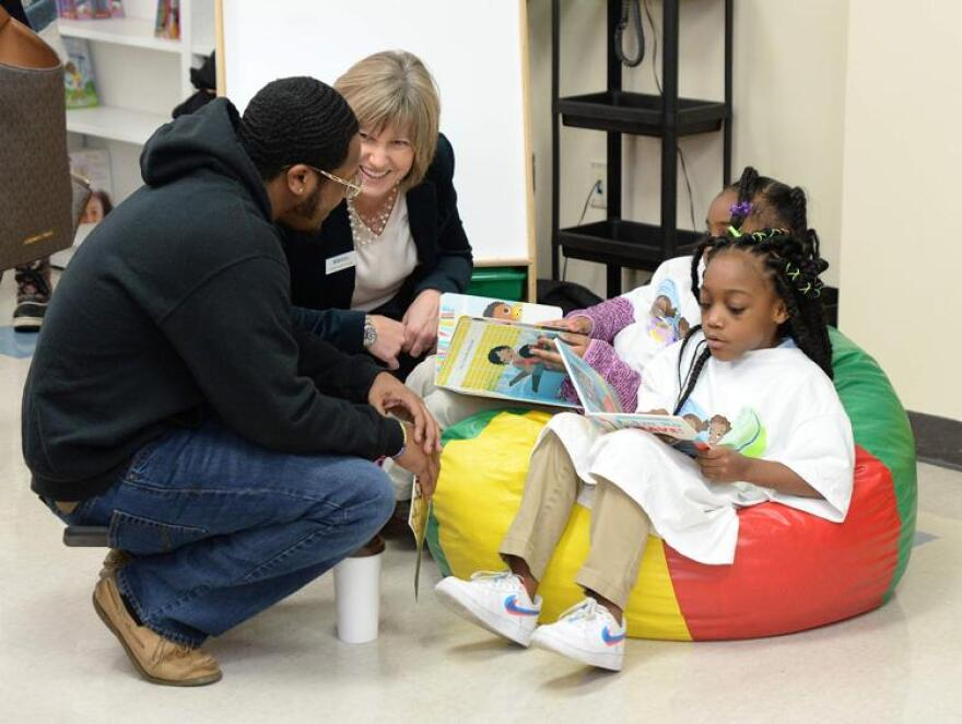 Tevin Wilson, a facilitator at Nine Network, and Angela Spittal, executive director of Ready Readers, talk with Confluence Academy-Old North first grade students Jermya Walker and Ziya Branom at the Believe Project reading room's grand opening on 12-19-19