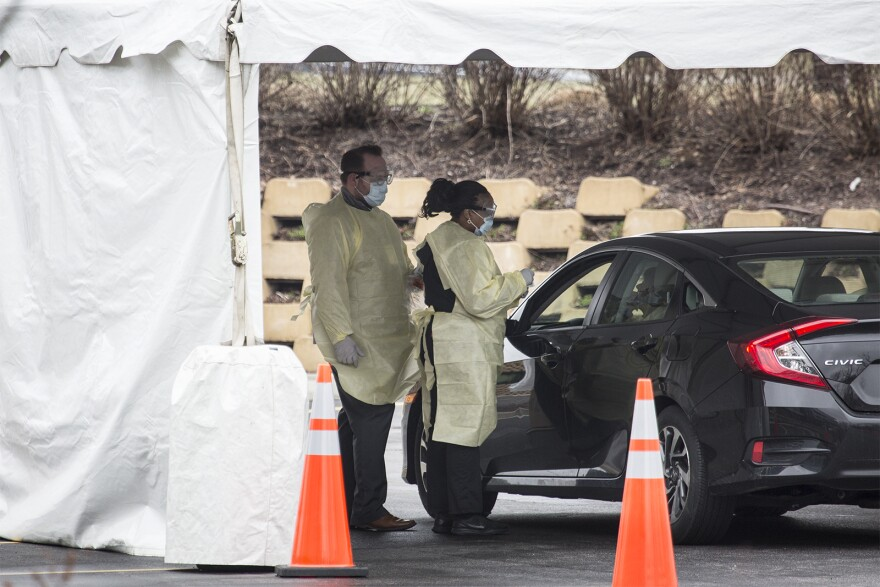 Medical workers collect a sample from a patient at Mercy Health's drive-through novel coronavirus test collection site in Chesterfield on Monday afternoon, March 16, 2020.