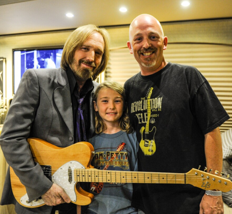 Jason Enright and his son, Connor, meeting Tom Petty on his tour bus in June 2013, with the guitar Jason made for Petty at Connor's urging.
