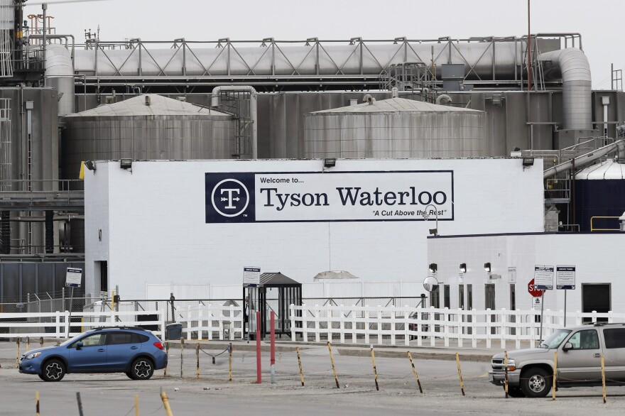 Vehicles sit in a near empty parking lot outside the Tyson Foods plant in Waterloo, Iowa, on May 1.