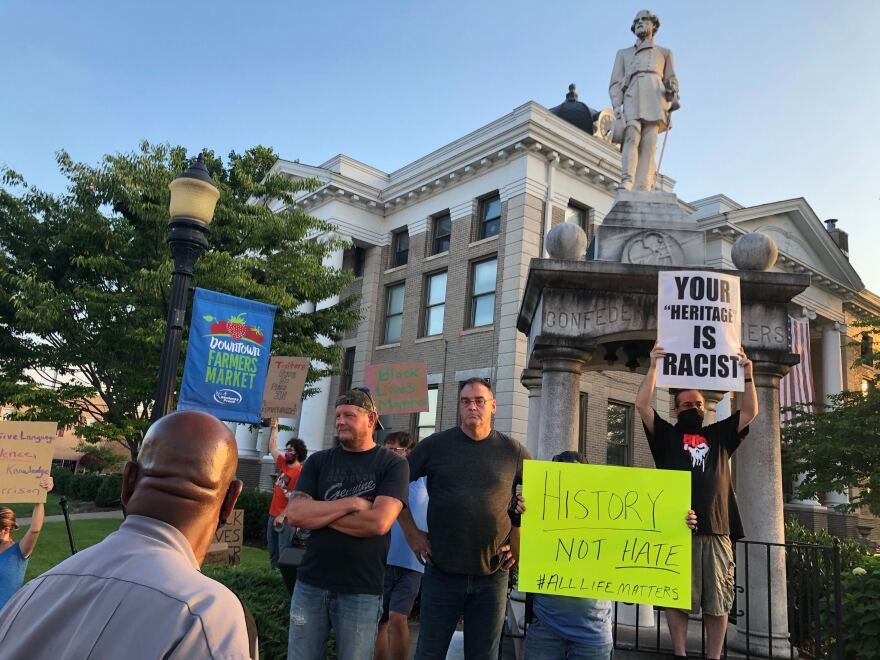 Protesters gather by the Confederate monument on county courthouse grounds
