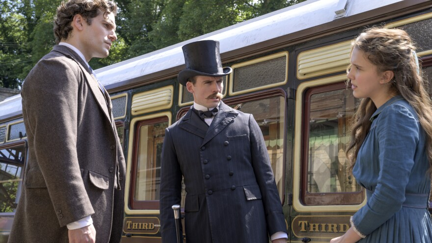 """""""The train's afoot!"""": (L to R) Sherlock (Henry Cavill) and Mycroft (Sam Claflin) literally look down on their younger sister Enola (Millie Bobby Brown) in Netflix's <em>Enola Holmes.</em>"""