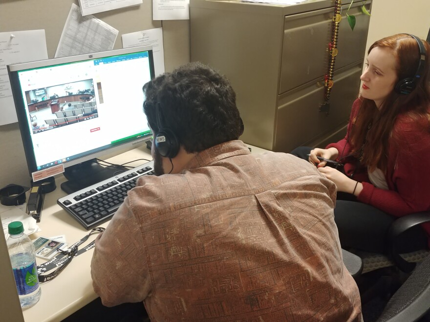 Two interns - one man, one woman - look at a video on a computer in a newsroom.