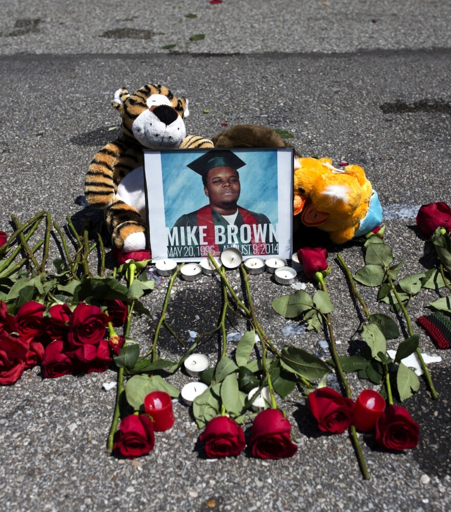 A dedication to Michael Brown Jr. A framed photo is surrounded by roses.
