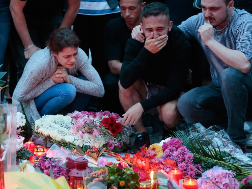 People mourn near a shopping center in Munich on July 23, the day after a shooting spree there left nine victims dead. The attack was one of several that month in Germany.