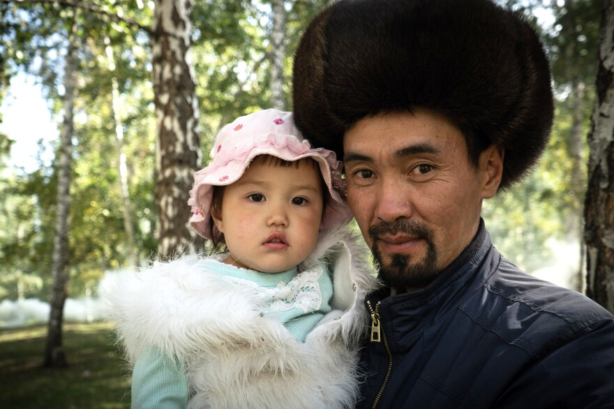 A Kyrgyz performer at the games poses with his daughter.
