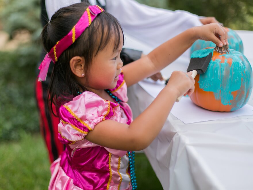 A young girl paints a pumpkin teal to signify that a place is safe for children with food allergies to go trick-or-treating.