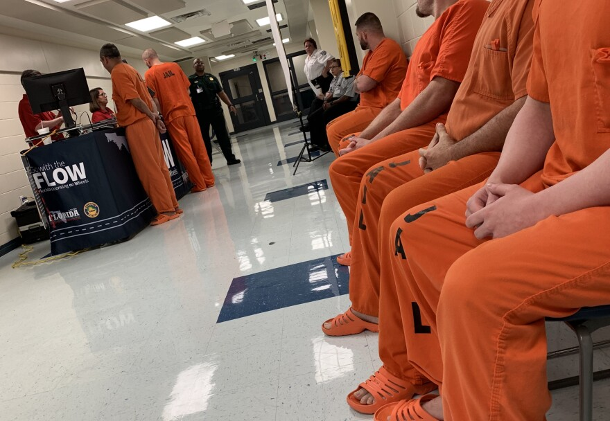Row of men in orange jumpsuits wait for ID
