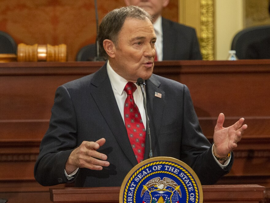 Man in a suit and red tie stands at podium with the Utah state seal.