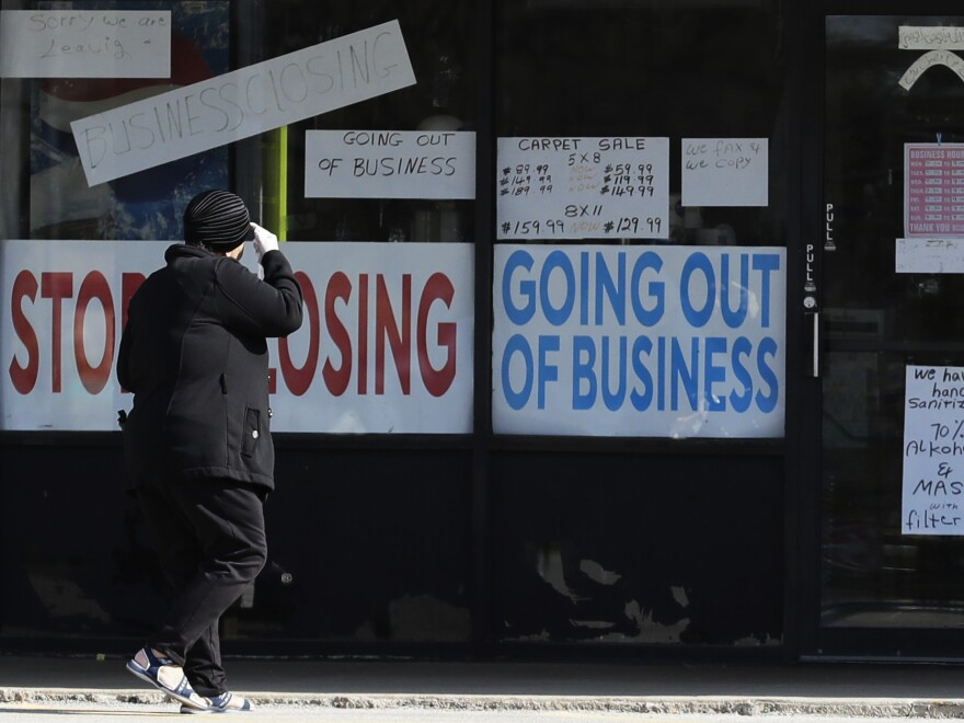 A woman looks at signs at a store in Niles, Ill., on May 13. Shutdowns related to the coronavirus pandemic have left tens of millions out of work.