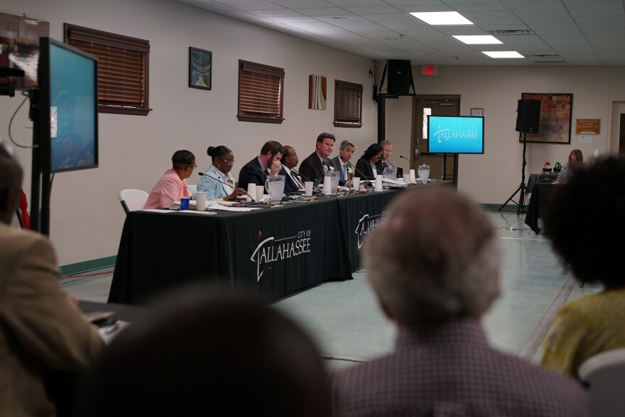 City Commissioners sit at a table covered in black table cloth. Two TV monitors are on opposite sides of the table and audience member's heads are seen in the foreground.