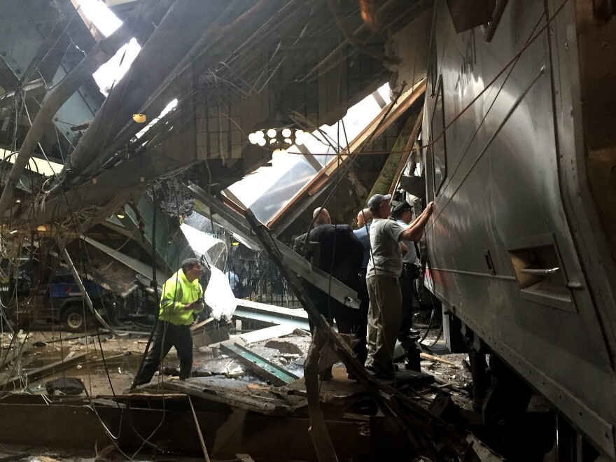 Train personnel survey the New Jersey Transit train that crashed into the platform at Hoboken Terminal on Thursday.