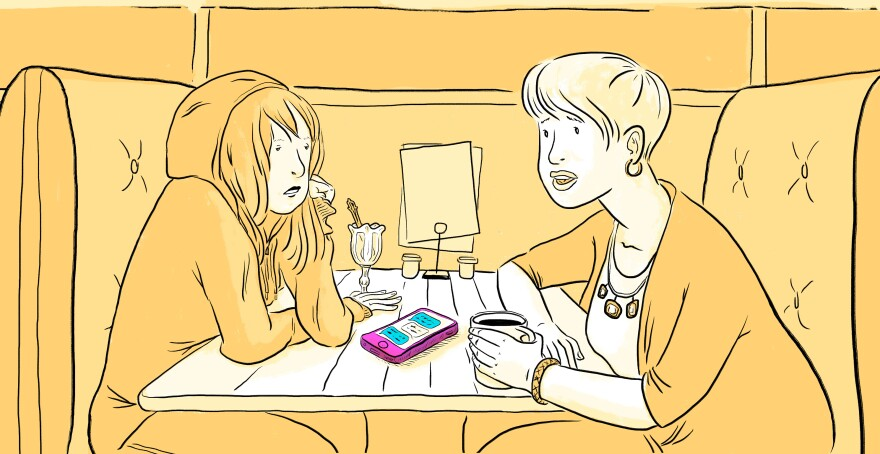 Mother and daughter discuss cell phone usage in a diner