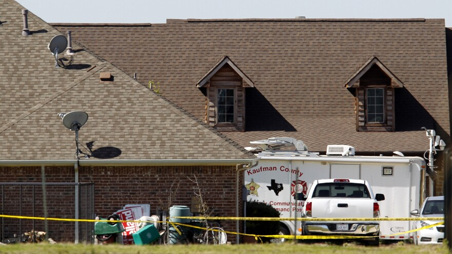 The home of Kaufman County District Attorney Mike McLelland is surrounded by police tape in Forney, Texas, on Monday. Authorities launched a massive investigation into the weekend killings of McLelland and his wife.