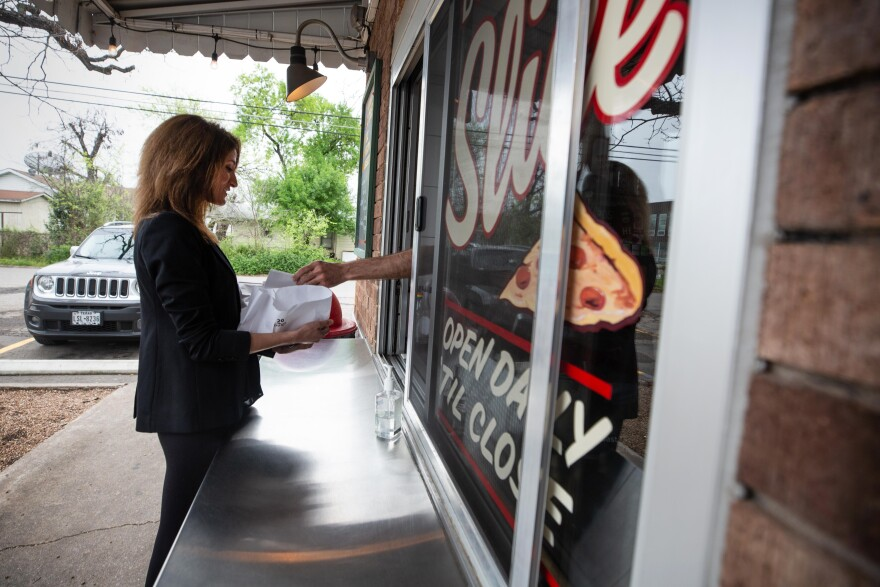 Jackie Romero picks up her lunch order at Home Slice Pizza in North Loop.