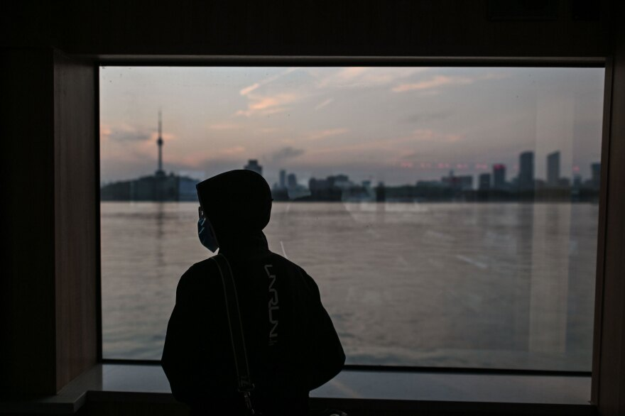 A man wearing a face mask travels on a ferry to cross the Yangtze River in Wuhan in April. Chinese officials are working to silence people suspected of challenging the narrative that authorities in Wuhan and Beijing acted swiftly and efficiently to contain the coronavirus outbreak.