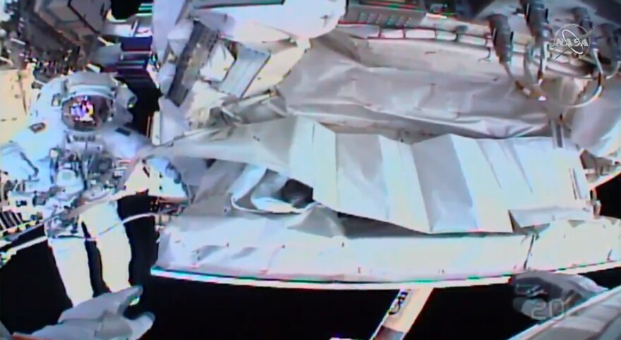 This photo provided by NASA shows the view from NASA's Andrew Morgan's helmet cam as Italian astronaut Luca Parmitano works outside the International Space Station during a spacewalk Saturday.