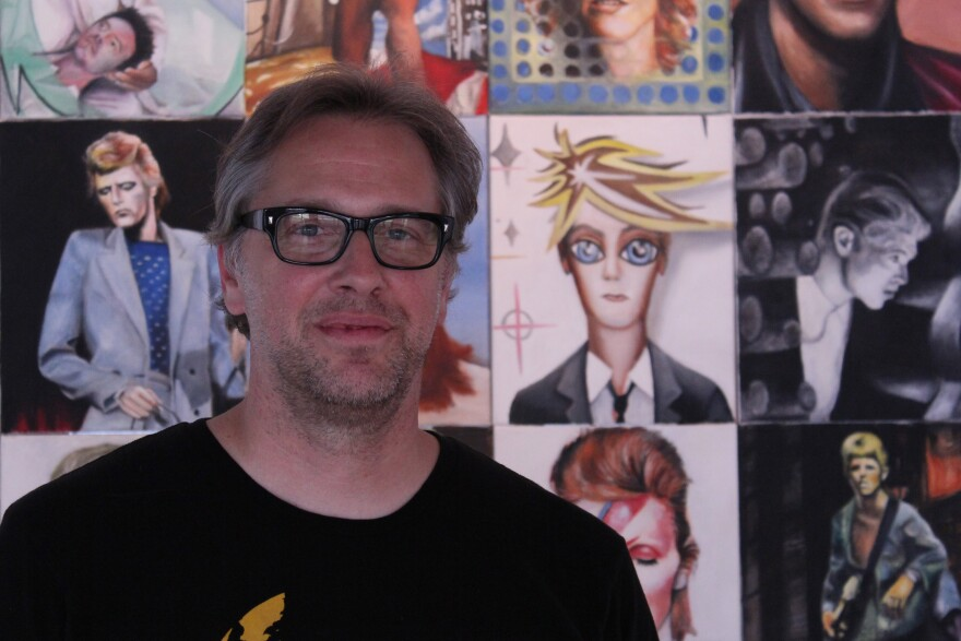 Mark Dethrow before a grid of multiple David Bowie portraits for Sound and Vision show