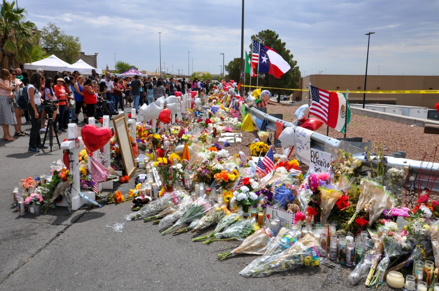 Flowers and candles line a memorial for the victims of the El Paso shooting outside the Walmart where the massacre happened on Aug. 3.