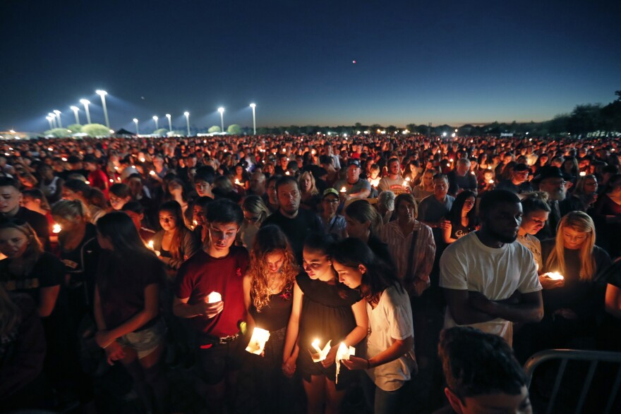 people attend a candlelight vigil for the victims of the shooting at Marjory Stoneman Douglas High School in Parkland, Fla.