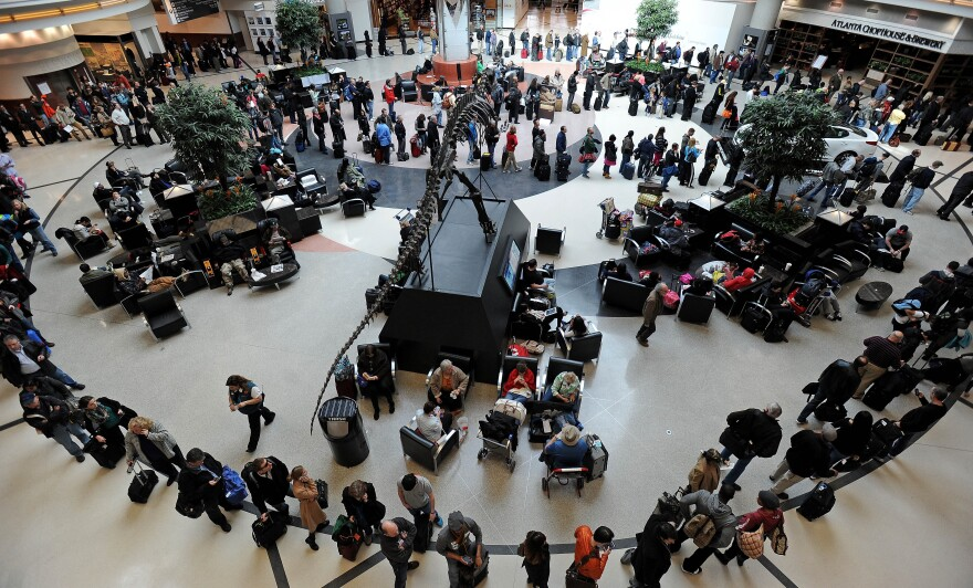 Passengers wait in line at Hartsfield-Jackson International Airport on Thursday. A major snowstorm has delayed flights from Atlanta to New York.
