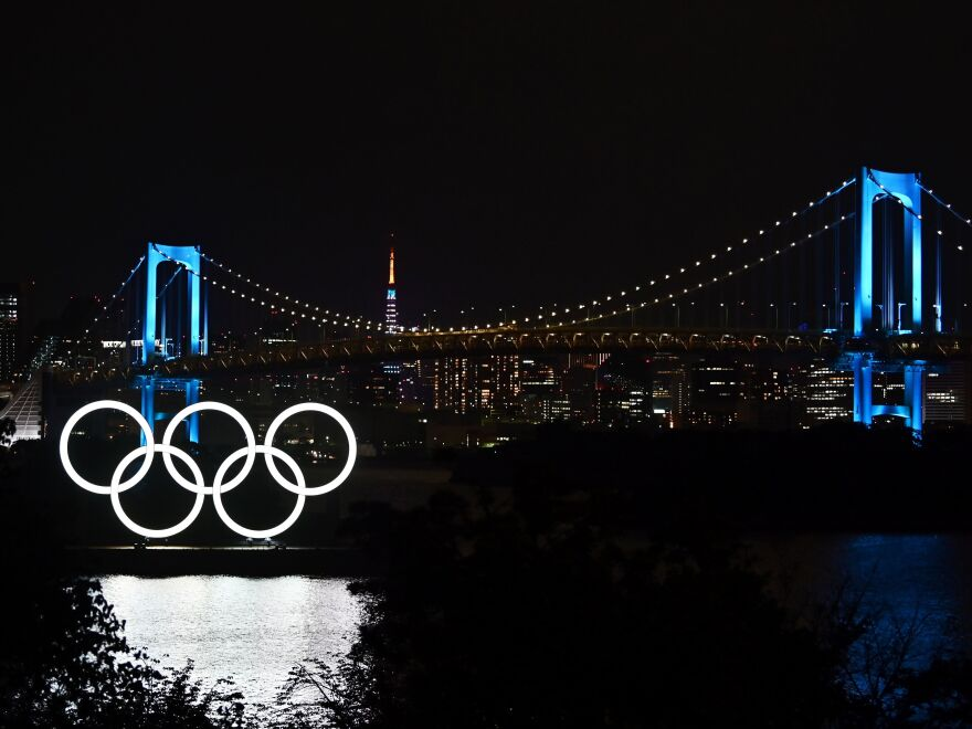 """""""We shall all need to make sacrifices and compromises"""" to put on the Tokyo 2020 Olympics, IOC President Thomas Bach says, announcing funding to help keep the delayed games on track. The Olympic rings, the Rainbow Bridge and the Tokyo Tower are seen in Tokyo Friday night."""