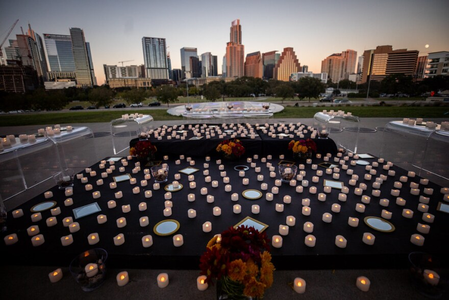 hundreds of battery operated tea light candles spread across several platforms at Austin's Long Center, looking out toward the Austin skyline