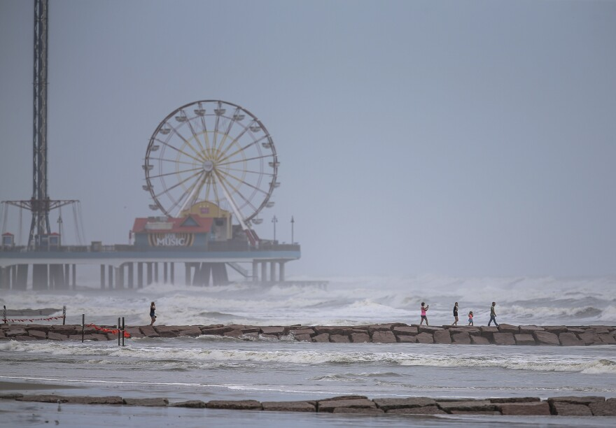 People walk along a jetty in Galveston, Texas, as waves roll in from Hurricane Laura as it approaches the U.S. on Wednesday.
