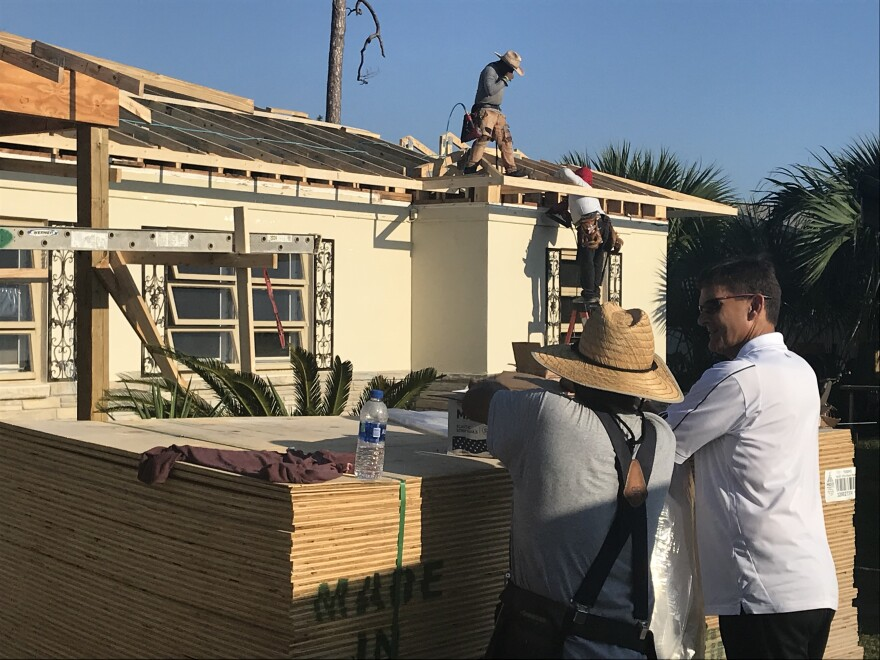 Contractors replace a roof on a Panama City resident's home almost one year after Hurricane Michael devastated the region.
