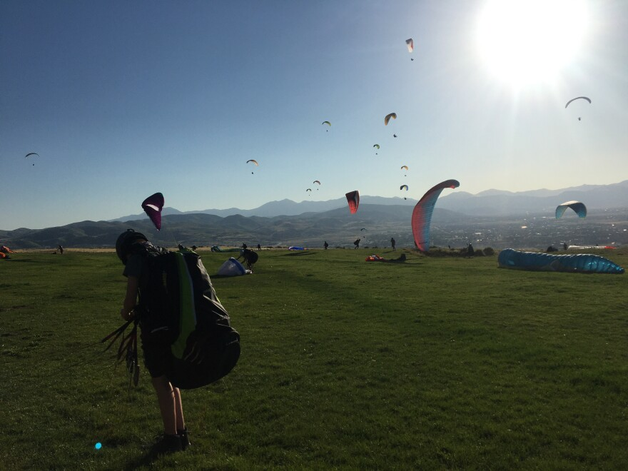 Photo of paragliders on a grassy hill.