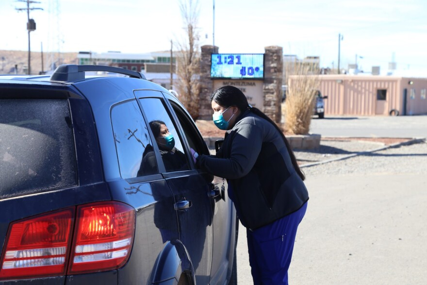 A woman in scrubs and a mask leans into a car window.