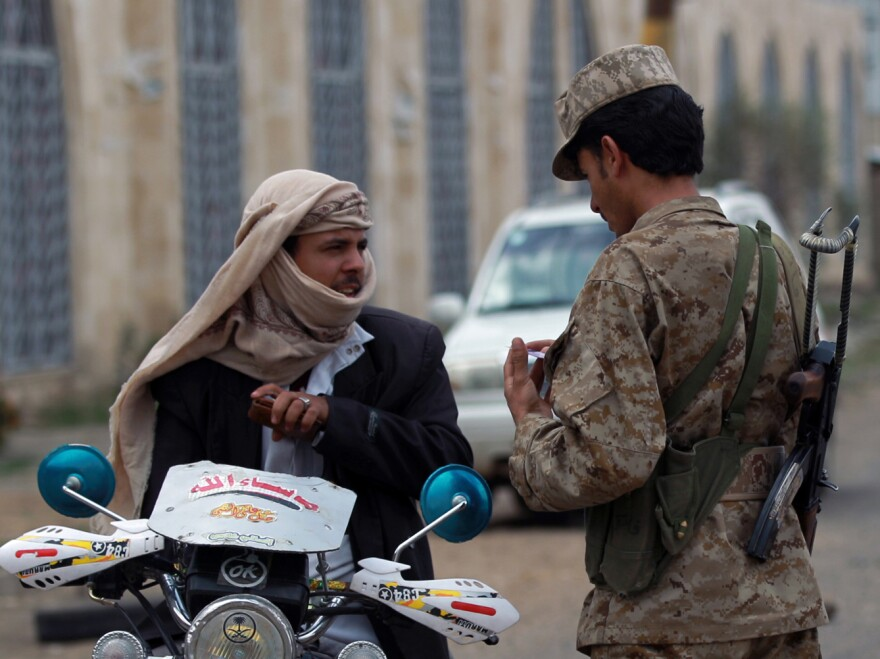 A Yemeni soldier speaks with a motorcyclist amid tightened security near Sanaa International Airport on Tuesday.