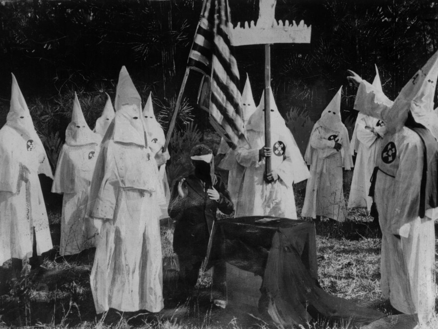 Members of the Ku Klux Klan ceremonially initiate a new recruit at a meeting in 1922.